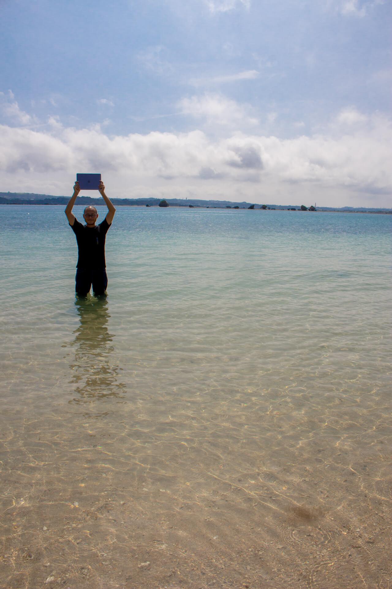 海と空とMacBookをかかげるたかひろ